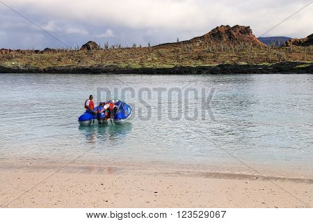 GALAPAGOS ECUADOR - APRIL 20: Unidentified men drive dinghy on April 20 2015 on Chinese Hat island in Galapagos National Park Ecuador. This park is a UNESCO World Heritage Site