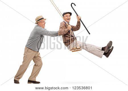Two joyful senior gentlemen swinging on a swing and having fun isolated on white background