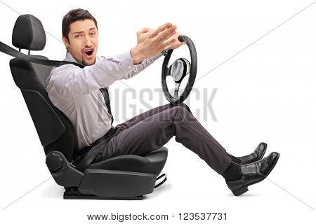 Angry young guy holding a steering wheel and arguing with someone isolated on white background