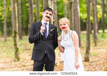 April Fools' Day. Wedding couple posing with stick lips, mask