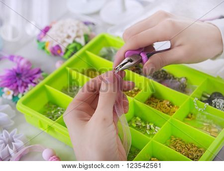 Accessories for needlework in container and tools for creating fashion jewelry in the manufacturing process. Jeweler making jewelry (bijouterie).Workshop. Hobby - Bijouterie Modeling.