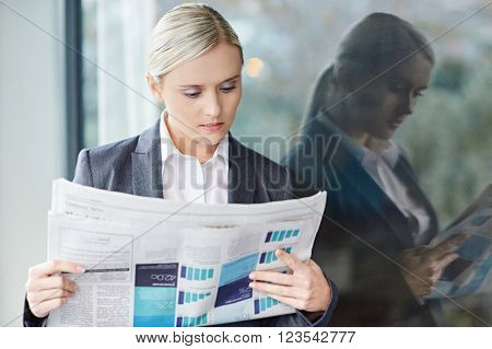 A young businesswoman reading the newpaper outside her office