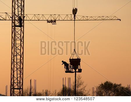 Silhouette of construction worker on the crane at sunset