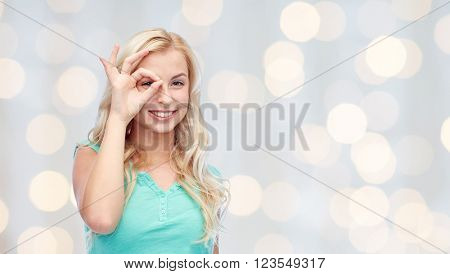 fun, emotions, expressions and people concept - smiling young woman or teenage girl making ok hand gesture over holidays lights background