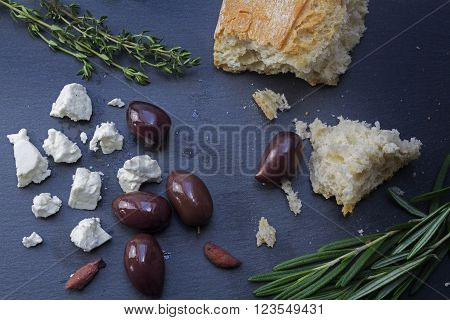 kalamata olives and feta cheese from Greece with bread and herbs spread out on a dark background of slate