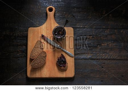 The top view of fruity jam and spoon and knife on black wooden table and bread poster