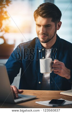 Working with joy. Cheerful young handsome man holding coffee cup and using his laptop with smile while sitting at his working place