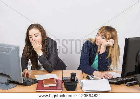 Two Young Office Employee Wearily Sitting Behind A Desk