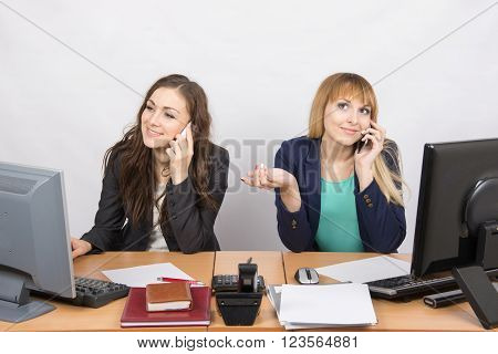 Two Girls At A Desk Talking On Mobile Phone In The Office