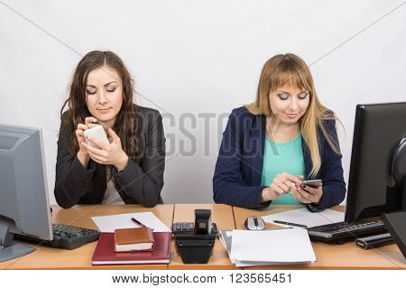 Office Workers Are Engaged In Private Affairs In Mobile Phones At His Desk