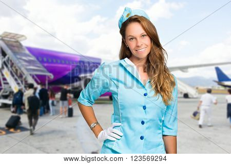Smiling hostess with airplane on the background
