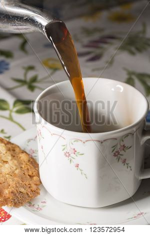 Coffey Pouring into Cup with cookie on the side