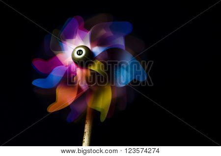 Colorful pinwheel toy on a black background