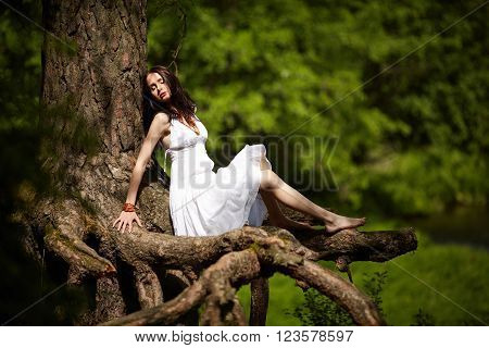 beautiful girl sitting on old tree roots