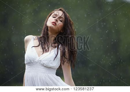 beautiful girl under rain in summer forest