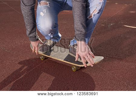Teenager doing exercises on a skateboard on the road