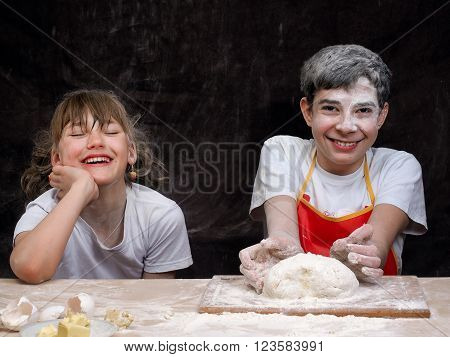 Teens knead the dough. Funny girl and the guy, mired in the flour. Baking Products. Cookware. Emotions, funny face. Relationship teens - friendship, love