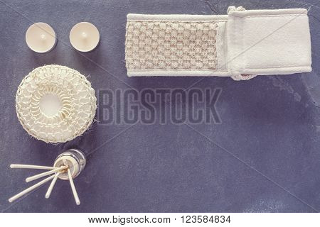 Vintage toned spa and wellness background with sponge, facecloth, aroma sticks and candles over dark stone background, copy space.