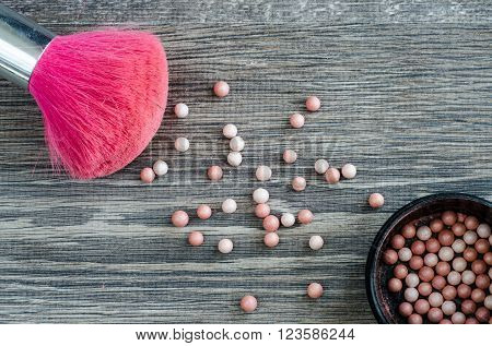 Pink brush for make-up and powder balls scattered on the wooden table