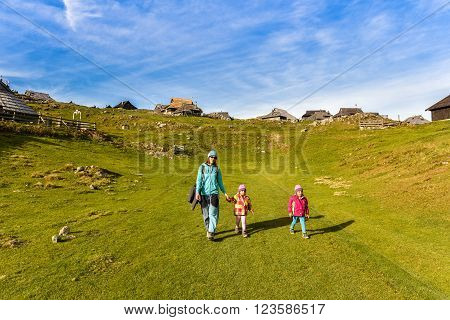Family hiking in the mountains on idyllic meadow on Velika Planina Slovenia. Mother and two twin children are hiking on the foot path in the nature in alps and hills. Active family .