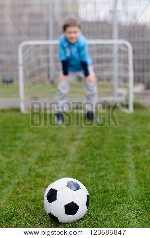 Football ball on grass and little soccer goalkeeper saving the goal. Child playing football