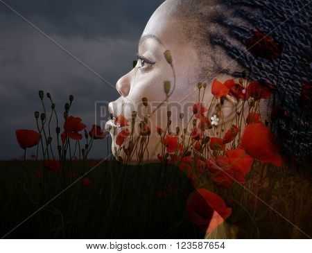 Double exposure portrait of beautiful woman. Beauty portrait of young african woman in profile with summer poppy flowers over dark gray background