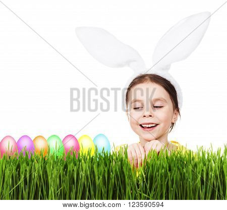 Little beautiful girl with rabbit ears on a white background. Green grass, colorful eggs. The concept of a happy Easter.