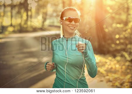 Runner in action at autumn under sunlight.