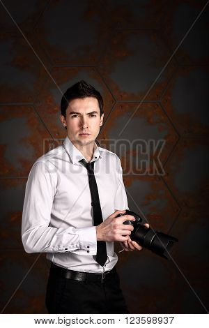 Professional photographer posing with photo camera in studio