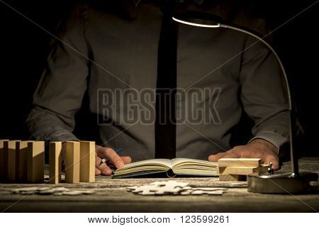 Front view of businessman working late hours sitting at his office desk making notes in notepad with pegs puzzles and dominos on the desk and lamp turned on.