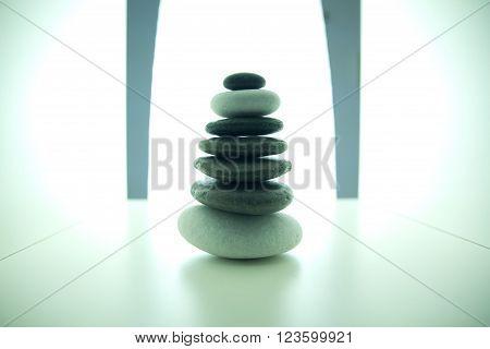 Balanced stone pile on a white surface