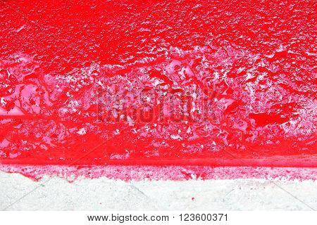Close up red-white kerb line or curb stone border on the asphalt road with wet paint. Footpath background.