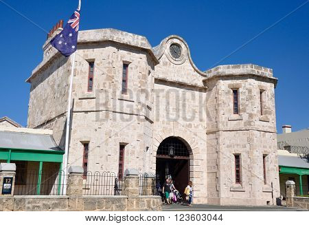 FREMANTLE,WA,AUSTRALIA-FEBRUARY 21,2015: Historic Fremantle Prison with limestone architecture, Australian flag and tourists under a blue sky in Fremantle, Western Australia.