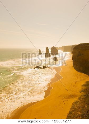 Beautiful sea waves run on the beautiful rocky coast of large stones along the Great Ocean Road and unusual rock twelve apostles of Victoria and unusual yellow light of sunset Australia