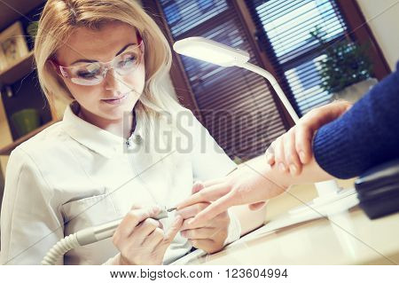 manicure specialist woman doing mail finger nail care