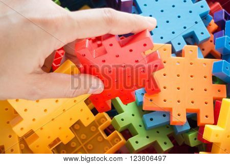 Hand on jigsaw puzzle game, stock photo