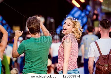 Teenagers at summer music festival against the stage in a crowd enjoying themselves, dancing and singing, back view poster