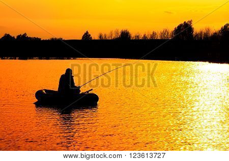 silhouette of a fisherman in a boat on a sunset background