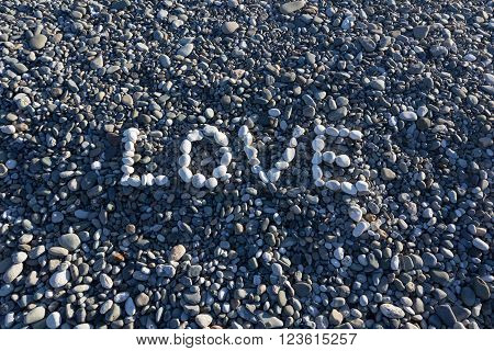The Sign Love Made From White Pebbles On Pebble Beach On The Sea