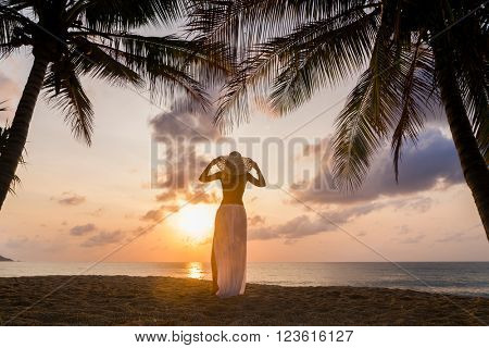 Woman on the tropical beach at sunset under the coconut trees
