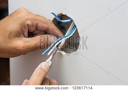 Man work with electric wires in hole of wall, copyspace.