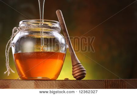 Pot is being filled with honey and a drizzler. Oblects are on wooden table.