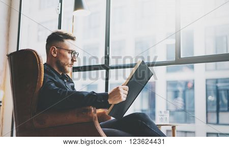 Portrait handsome bearded businessman wearing glasses, black shirt.Man sitting in vintage chairmodern loft studio, reading book and relaxing. Blurred background, film effect.