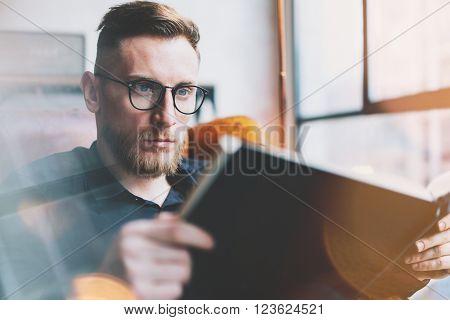 Portrait handsome bearded businessman wearing glasses, black shirt.Man sitting in vintage chair modern loft studio, reading book and relaxing.Time break. Blurred background, film effect.