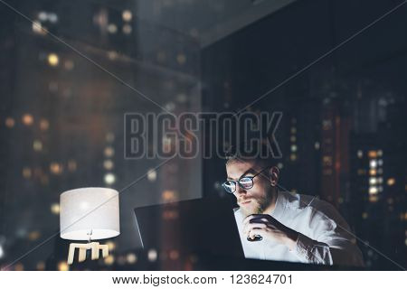 Bearded young businessman working on modern loft office at night. Man using contemporary notebook texting message, holding cup espresso, blurred background, bokeh