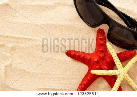 Sea Stars And Sun Glasses On The Sand