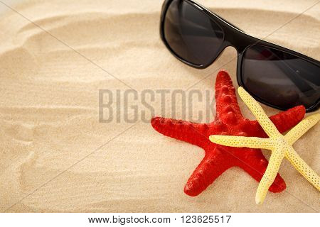 Sea Stars And Sun Glasses On The Sand
