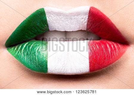 Female lips close up with a picture flag of Italy. Green, white, red