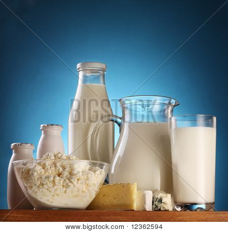 Different milk products: cheese; cream; milk. On a blue background.