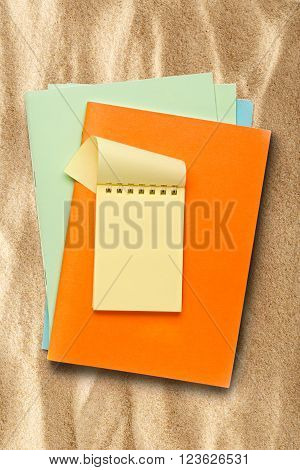 Open Yellow Notepad On Colored Pieces Of Paper